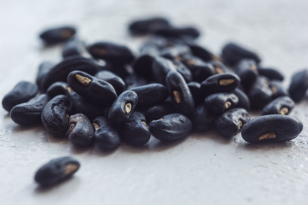A heap of dried black haricot seeds close-up on a white table background. bean sowing season. close up top view copy space.