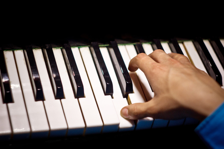 one male hand on the piano. The palm lies on the keys and plays the keyboard instrument in the music school. student learns to play. hands pianist. black dark background. Imagens