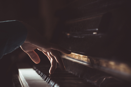 one male hand on the piano. The palm lies on the keys and plays the keyboard instrument in the music school. student learns to play. hands pianist. black dark background.