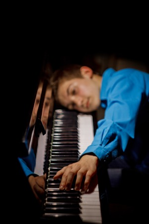 young man sitting at the piano. the boy lies on the keys and plays the keyboard instrument in the music school. student learns to play. hands pianist. black dark background. vertical.