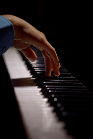 one male hand on the piano. The palm lies on the keys and plays the keyboard instrument in the music school. student learns to play. hands pianist. black dark background. vertical.