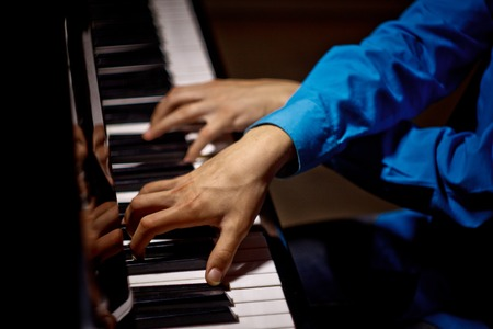 two male hands on the piano. palms lie on the keys crosswise and play the keyboard instrument in the music school. student learns to play. hands pianist. black dark background. top view. 写真素材