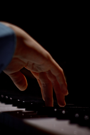 one male hand on the piano. The palm lies on the keys and plays the keyboard instrument in the music school. student learns to play. hands pianist. black dark background. vertical. Stock Photo