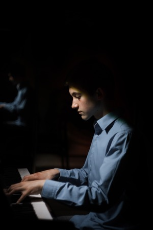 young man sitting at the piano. boy emotionally plays the keyboard instrument in the music school. student learns to play. hands pianist. black dark background. vertical.