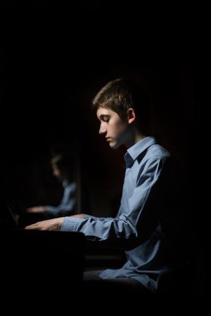 junger Mann sitzt am Klavier. Junge spielt emotional das Tasteninstrument in der Musikschule. Schüler lernt spielen. Hände Pianist. schwarzer dunkler Hintergrund. vertikal.
