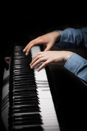 two male hands on the piano. palms lie on the keys and play the keyboard instrument in the music school. student learns to play. hands pianist. black dark background. vertical.