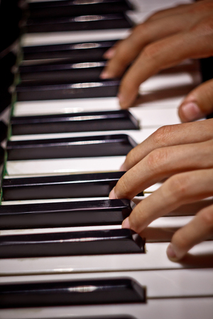 two male hands on the piano. palms lie on the keys and play the keyboard instrument in the music school. student learns to play. hands pianist. black dark background. top view. vertical. Foto de archivo
