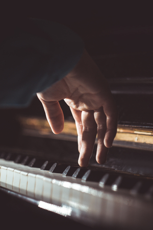 one male hand on the piano. The palm lies on the keys and plays the keyboard instrument in the music school. student learns to play. hands pianist. black dark background. vertical. 写真素材