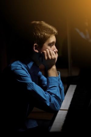 young man sitting at the piano. the boy wondered how he played the keyboard instrument in a music school. student learns to play. hands pianist. black dark background. vertical.