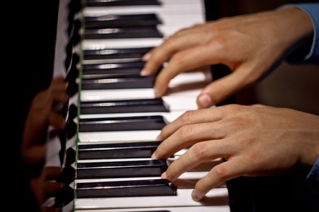 two male hands on the piano. palms lie on the keys and play the keyboard instrument in the music school. student learns to play. hands pianist. black dark background. top view.