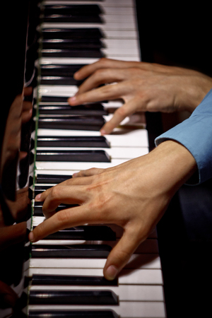 two male hands on the piano. palms lie on the keys crosswise and play the keyboard instrument in the music school. student learns to play. hands pianist. black dark background. top view. vertical. 写真素材