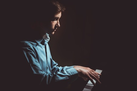 young man sitting at the piano. boy emotionally plays the keyboard instrument in the music school. student learns to play. hands pianist. black dark background.