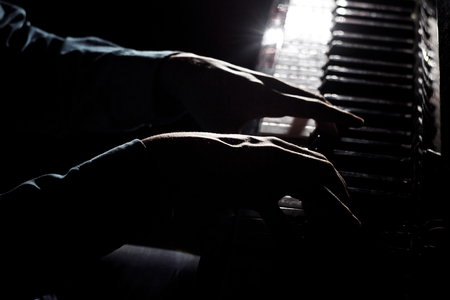 two male hands on the piano. palms lie on the keys and play the keyboard instrument in the music school. student learns to play. hands pianist. black dark background. 版權商用圖片 - 122128325