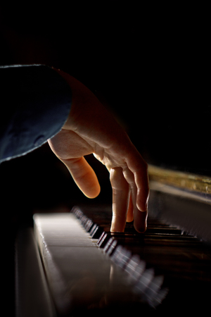 one male hand on the piano. The palm lies on the keys and plays the keyboard instrument in the music school. student learns to play. hands pianist. black dark background. vertical. Stockfoto
