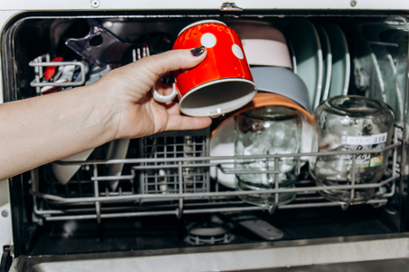 Female hand lays the dishes in an open dishwasher close-up clogged with clean, washed dishes. dry cutlery closeup. spoons forks. mugs, plates. household appliances in the kitchen.