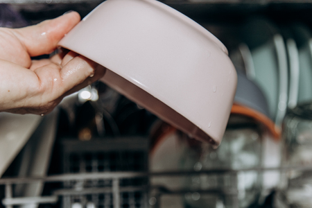 Female hand lays the dishes in an open dishwasher close-up clogged with clean, washed dishes. dry cutlery closeup. spoons forks. mugs, plates. household appliances in the kitchen. Banco de Imagens