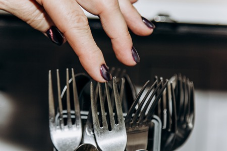 Female hand lays the dishes in an open dishwasher close-up clogged with clean, washed dishes. dry cutlery closeup. spoons forks. mugs, plates. household appliances in the kitchen. 写真素材