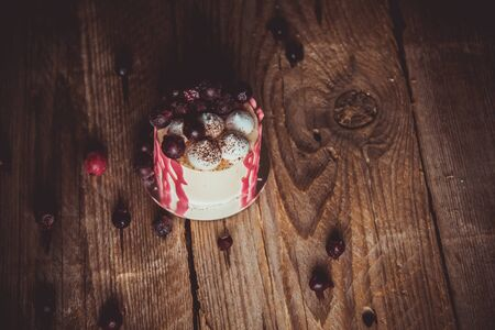 festive cake with the fruits of cherry on a rustic wooden table on a dark background. close up copy space. vintage pattern on dessert tartlet. birthday holiday. Stock fotó
