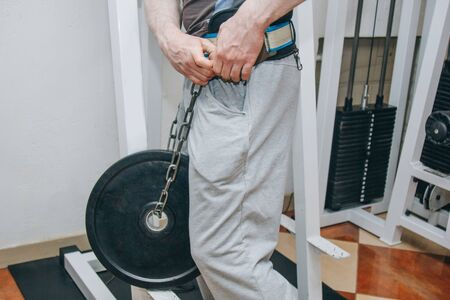 athlete doing exercise with weight on the waist belt in the center of training. training tools in the gym close-up.