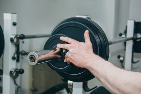 an athlete with big hands adds weight by the metal disks to the training apparatus in the training center. training equipment in the gym close-up. 스톡 콘텐츠