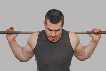 Un athlète bien entraîné entraîne les muscles de ses jambes dans un centre d'entraînement. squats d'haltères dans la salle de gym.