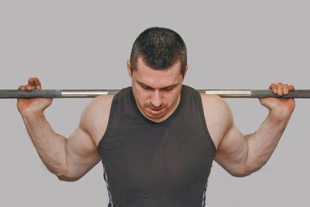 Un atleta bien entrenado entrena los músculos de sus piernas en un centro de entrenamiento. sentadillas con barra en el gimnasio.