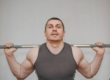 A well-trained athlete trains his leg muscles at a training center. barbell squats in the gym. Standard-Bild