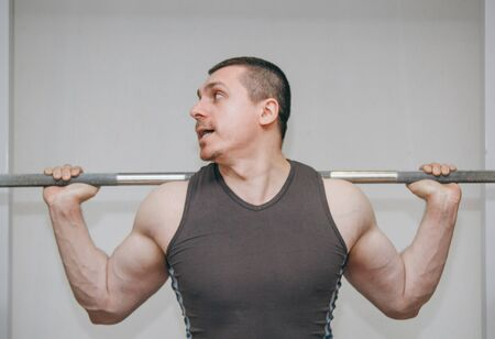A well-trained athlete trains his leg muscles at a training center. barbell squats in the gym. Stock Photo