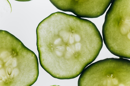 green translucent slices of cucumber on the background of bright white light close-up. transparent discs of vegetables. texture of kaleidoscope patterns in macro. Stock fotó