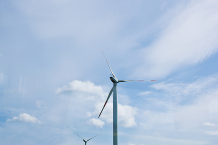 wind power plant on the background of bright cloudy sky. wind generator close-up. green electricity, alternative energy.