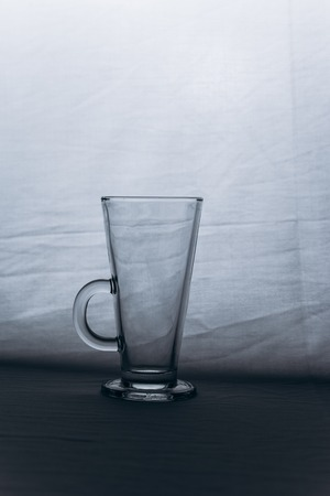 empty transparent glass cup on a gray silver background close-up. high cup with handle and leg. copy space, texture, background. vertical. Stock Photo - 123962825