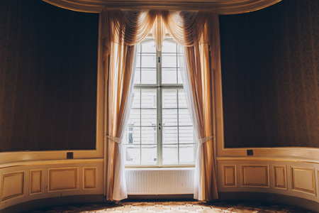 wooden windows with vintage curtains and square moldings on a sunny day. beige satin curtains. interior of an empty room with expensive decoration. background for collage.
