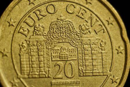 coin twenty euro cent macro isolated on black background. Detail of metallic money close up. EU money.