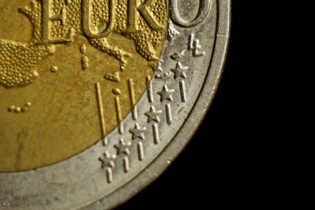 two euro coin close up isolated on black background. Detail of metallic money close up. EU money. Stock Photo