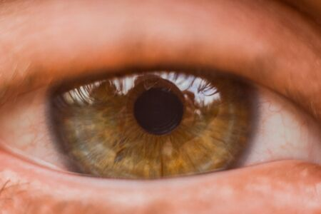 male eye close up. man looks into the frame. brown iris in macro. Stock Photo