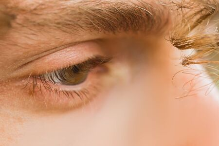 male eye close up. a curl of curly hair hangs over a mans face. thoughtful look into the void.