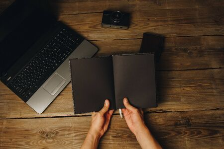 workplace blogger. set to prepare for public speaking and writing text: keyboard and phone on a wooden table, top view. freelancer writes the text in a notebook. Stock Photo