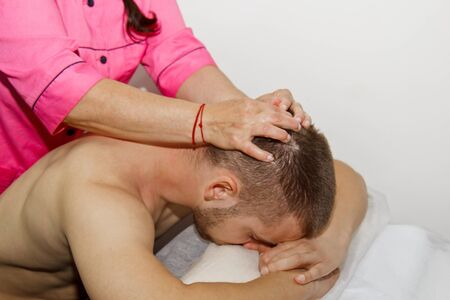 professional therapeutic neck and head massage. man the athlete in a massage room. pain recovery procedure. Female physiotherapist doing manipulative spine treatment on young patient.