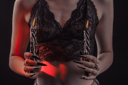 Female hands with long nails hold burning candles on a black isolated background. concept of witchcraft witchcraft on halloween. silver rings on the fingers. sexy slim girl in lace bra. 版權商用圖片