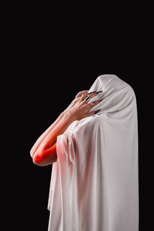 a woman covered with white cloth with a closed face suffers. faceless pain. long black nails on thin female fingers. emotion without facial expressions.