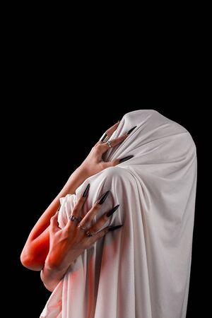 sufre una mujer cubierta de tela blanca con el rostro cerrado. dolor sin rostro. uñas largas y negras en finos dedos femeninos. emoción sin expresiones faciales. Foto de archivo