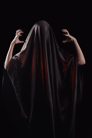 a woman covered with black cloth with a closed face suffers. faceless pain. long black nails on thin female fingers. emotion without facial expressions. Stock fotó