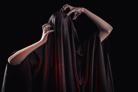 sufre una mujer cubierta de tela negra con el rostro cerrado. dolor sin rostro. uñas largas y negras en finos dedos femeninos. emoción sin expresiones faciales. Foto de archivo