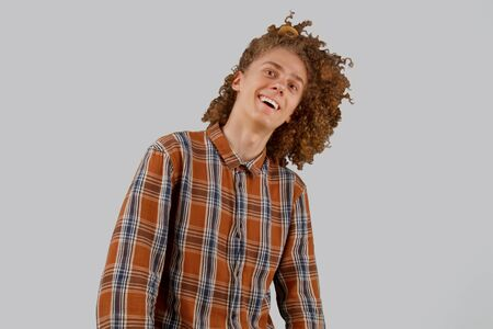 Portrait of a curly-haired young man with a wooden comb in full hair smiling on a gray isolated background. male hair care concept.