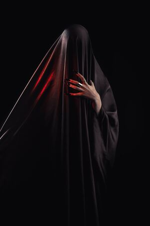 woman covered with black cloth stands on an isolated black background. faceless death concept. Reklamní fotografie