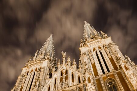 Catholic church on a background of a strange sky. Gothic building with sharp spiers against the backdrop of scary clouds at night illuminated by a lantern. Stockfoto