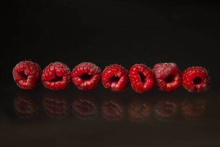 berries of red raspberries in a bunch lie on a black glass top view. sweet summer berries. Banque d'images - 129962313