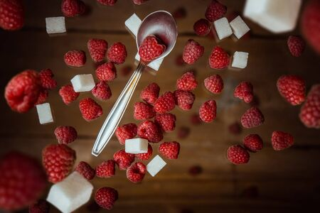 berries of red raspberries with a teaspoon and cubes of refined sugar lie on a wooden rustic table top view. Banque d'images - 129962332