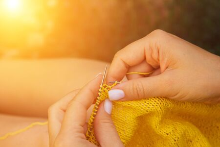 a young girl with long blond hair knits a yellow sweater in the garden in the summer. woman makes clothes with hands closeup. Standard-Bild - 129964405