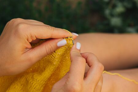 a young girl with long blond hair knits a yellow sweater in the garden in the summer. woman makes clothes with hands closeup. Standard-Bild - 129964407